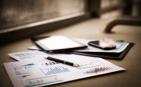 close up of paper documents with business charts and tablet on a table