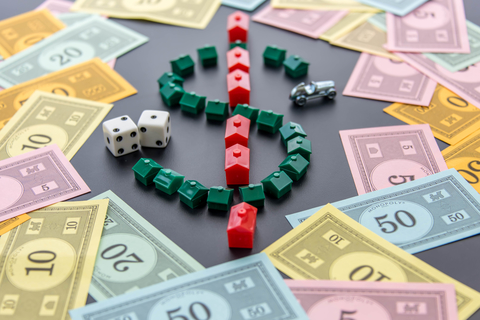 A dollar sign created by Monopoly game houses is surrounded by Monopoly money. Dice and the car token appear next to the dollar sign as well.