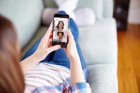 woman on couch uses telehealth app to talk to doctors