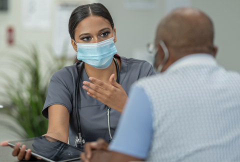 A female doctor speaks to a male patient