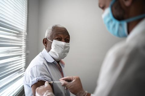 A nurse administers a vaccine into a man's arm