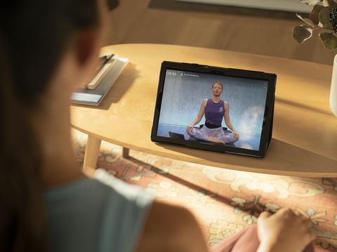 woman doing meditation exercises with laptop screen showing Peloton app