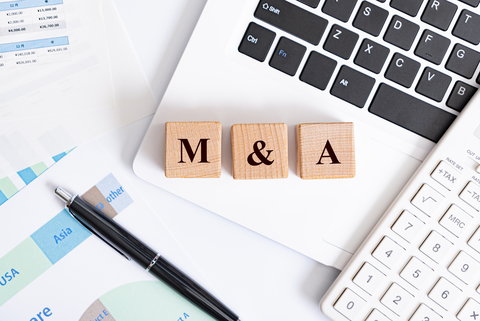 M&A concept - M&A word made with wooden blocks on laptop