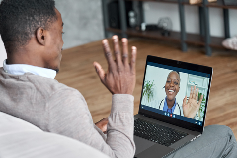 Black patient talking on conference video call to female doctor