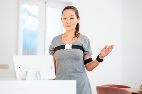 a woman stands in front of a computer screen using a virtual physical therapy program