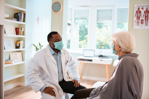 A male primary care doctor and his patient sit across from each other talking. Both are wearing masks