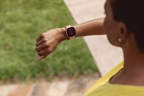 woman checks Fitbit fitness tracker