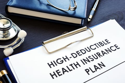 """A clipboard with a paper reading """"High-deductible health insurance plan"""""""