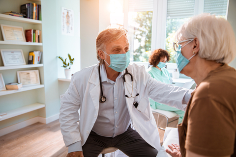 A doctor treats an older woman while they wear facemasks