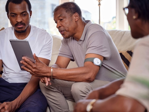 a male patient with a remote monitoring wearable on his arm uses a tablet to interact with his doctor