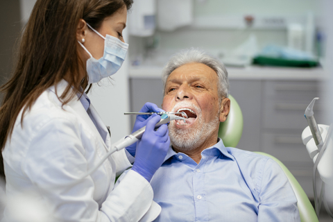 An elderly man is treated at the dentist