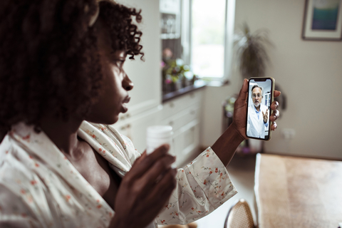 young woman consulting with doctor using smartphone for telehealth visit