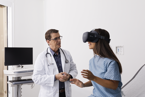 A doctor speaks to a female patient wearing a VR headset