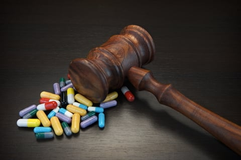 Wooden gavel over small pile of multi-colored pills on dark background.