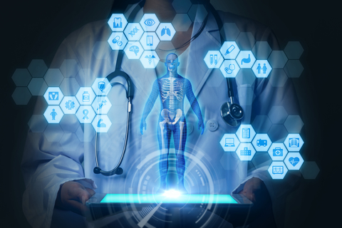 Physician wearing lab coat and stethoscope holding tablet. On top of tablet, there is a holographic skeleton diagram surrounded by hexagons with health symbols inside them, such as an ambulance, an x-ray, and a pill bottle.