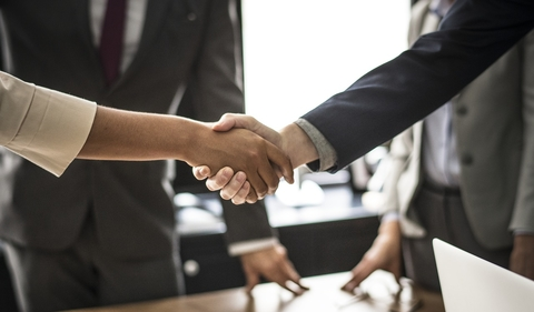 Close-up of two people shaking hands with other people in the background