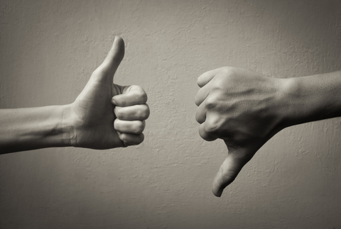Black-and-white image of a thumbs-up hand and a thumbs-down hand in front of a blank wall.