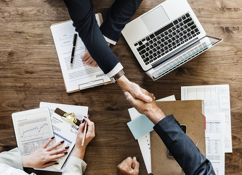 People shaking hands across a desk that has computer and papers on it