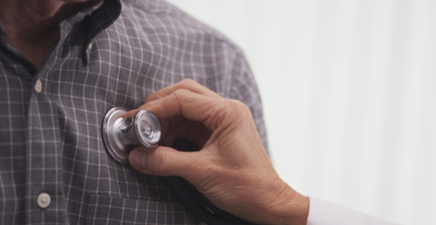 Doctor putting stethescope to patient's chest