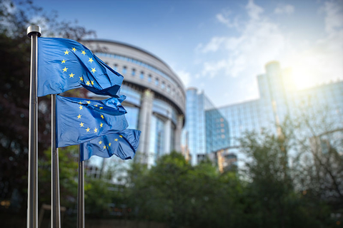 European Union flags waving in front of the EU Parliament building in Brussels