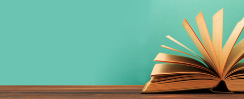 Open book with pages fanned against a turquoise background