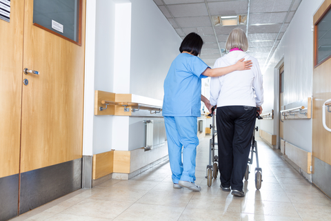 A senior woman and female nurse in the hallway of a nursing home