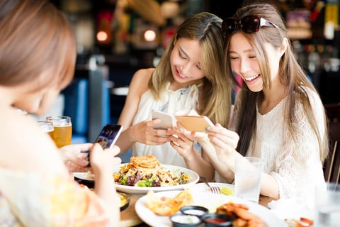 Two women taking pictures of their food