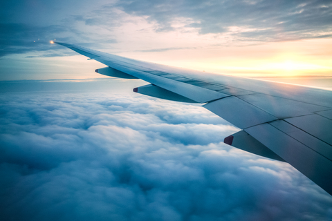 TIp of aircraft wing inflight with blue sky and clouds