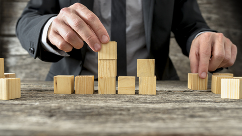 man in suit stacking blocks