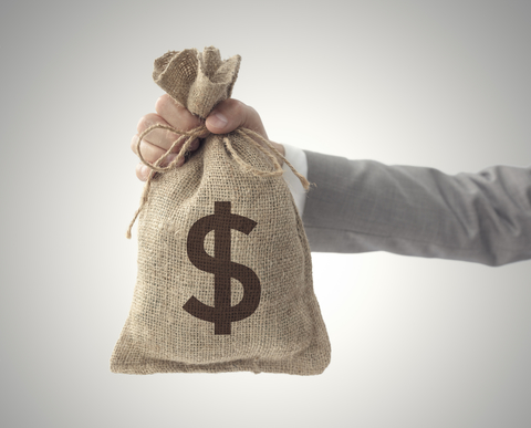 A person holds out a bag of money