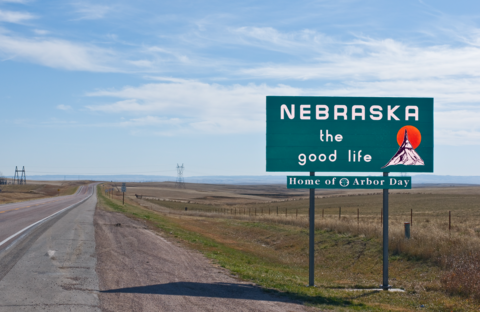 A picture of the Nebraska state sign by the side of a rural road