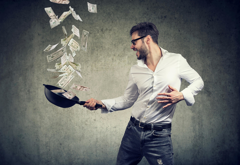Man tossing money in a frying pan