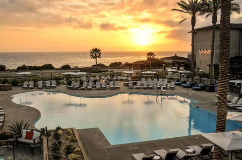The pool area with the sun setting over the ocean in the background
