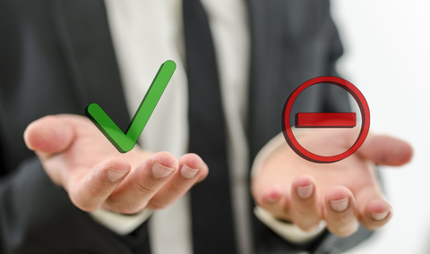 Businessman with positive and negative symbols in hand