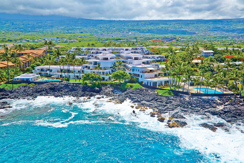 resort buildings set in the hills next to a beach in Hawaii
