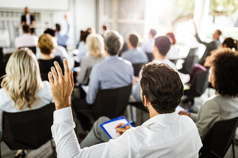 A man raises his hand at a conference.