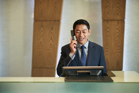 Front desk hotel employee on the phone