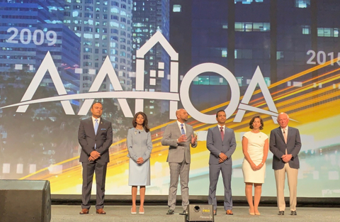 The AAHOA executives stand on stage