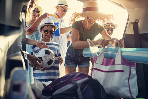 family packing a car for road trip vacation