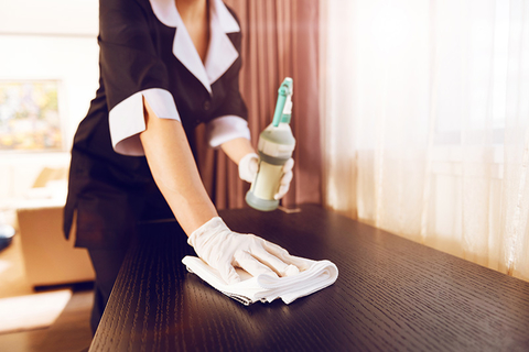woman with gloves cleaning counter