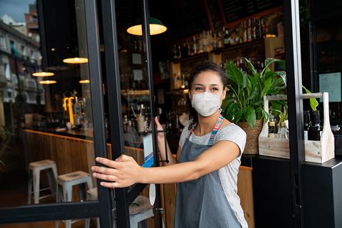 Woman wearing mask, opening door to restaurant