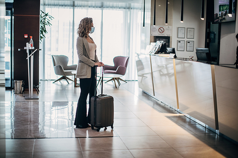 Woman with face mask at hotel front desk