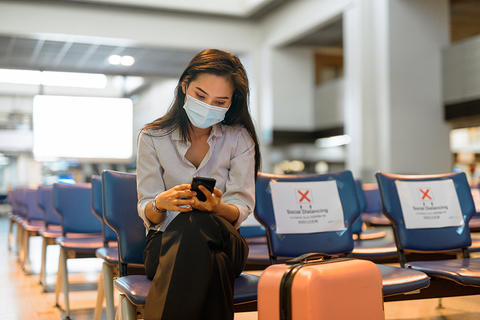 Woman at airport with mask and luggage