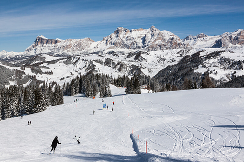 Skiers going down a mountain in Alta Badia Dolomites Italy
