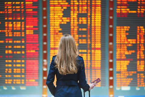 woman at airport looking at information board