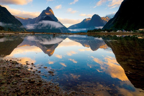 Mountains and clouds are reflected in water