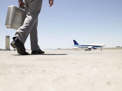 Businessman Walking Toward Airplane