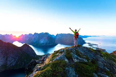 Happy woman hiker enjoying scenic view of midnight sun at the top of Reinebringen hike above Reine village in the Lofoten archipelago during arctic summer, Norway