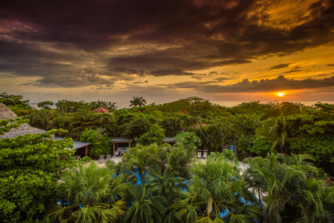 A view above Cala Luna Boutique Hotel & Villas with the sun setting over the water