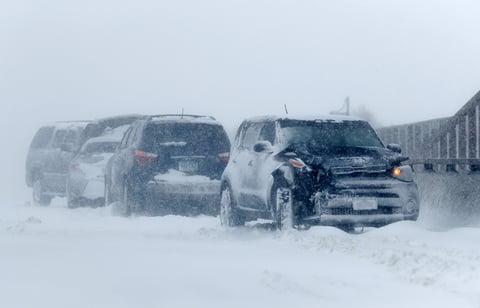 A string of wrecked vehicles sit on an overpass over Interstate 70 as a late winter storm packing hurricane-force winds and snow sweeps over the intermountain region.
